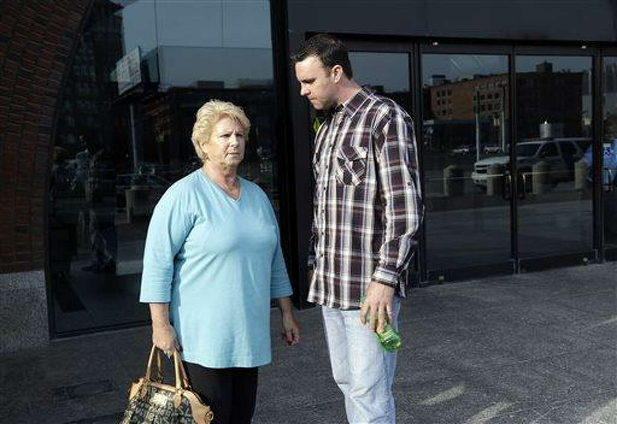 """Patricia Donahue, widow of alleged murder victim Michael Donahue, stands with her son, Tommy, outside federal court in Boston, Monday, June 3, 2013, after a pre-trial hearing for accused mobster James """"Whitey"""" Bulger. Jury selection begins Tuesday. (AP Photo/Elise Amendola)"""