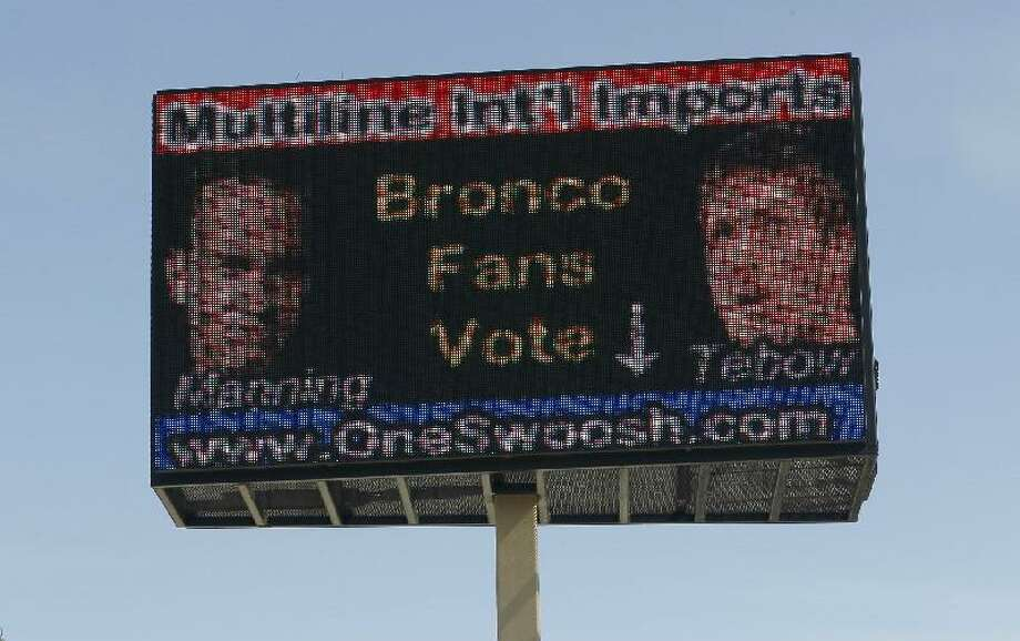 ASSOCIATED PRESS An electronic billboard located over a memorabilia store in north Denver urges fans to cast a ballot for either Peyton Manning, shown left, or Tim Tebow as the quarterback for the Denver Broncos on Saturday. Manning, who was released from the Indianapolis Colts this week, was in Denver on Friday to visit with Broncos officials in an effort to find a new place to play in the NFL.