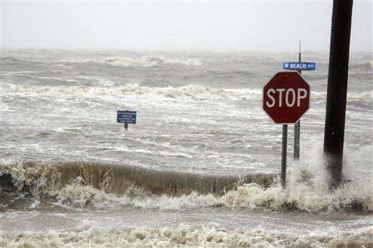 Isaac's winds and storm surge overcomes the seawall and floods Beach Boulevard in Waveland, Miss., Wednesday, Aug. 29, 2012, the seventh anniversary of Hurricane Katrina hitting the Gulf Coast. (AP Photo/Rogelio V. Solis)