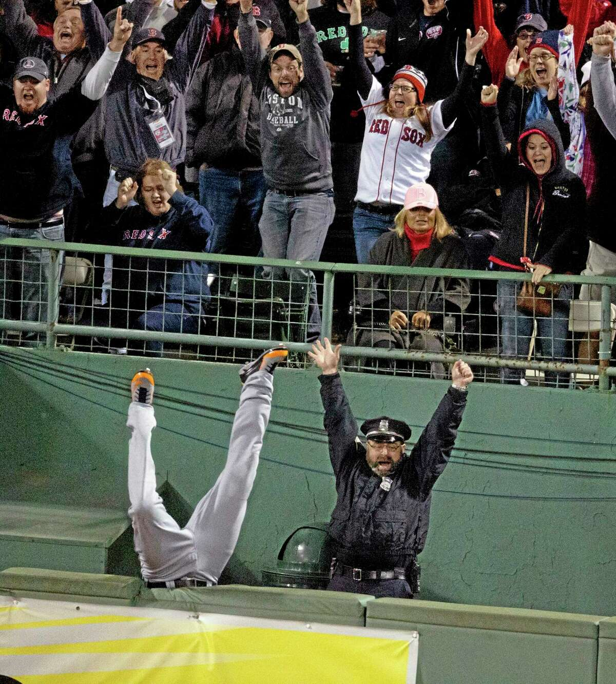 Fans and Boston police officer Steve Horgan celebrate as Detroit Tigers right fielder Torii Hunter falls over the fence into the bullpen trying to catch a grand slam hit by Red Sox designated hitter David Ortiz in Game 2 of the American League championship series on Sunday night in Boston.