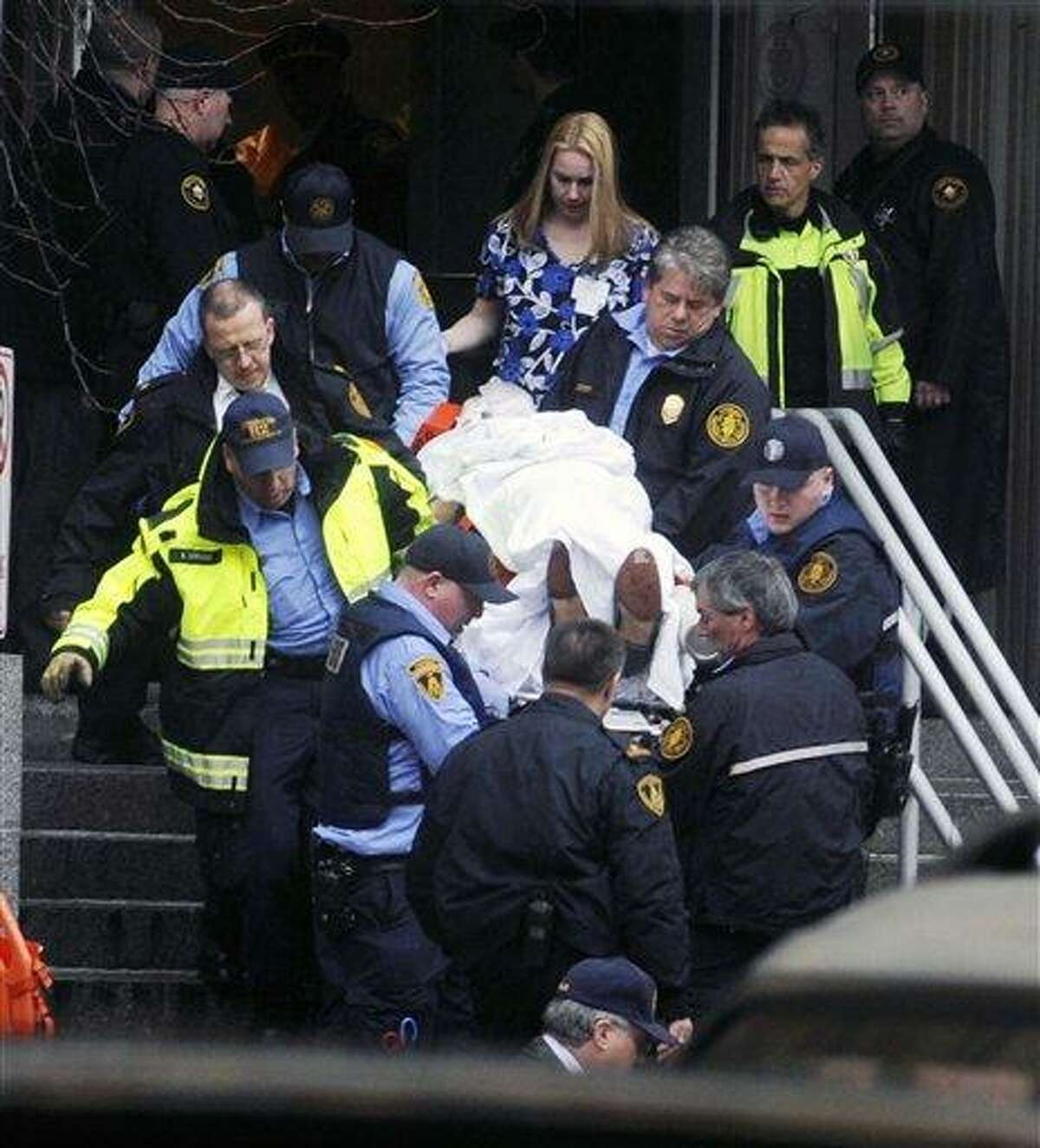 Paramedics and police carry a shooting victim from Western Psychiatric Institute and Clinic Thursday, in Pittsburgh. A gunman opened fire at the psychiatric clinic at the University of Pittsburgh in a shooting that killed two people, including the gunman, and wounded seven others. Associated Press