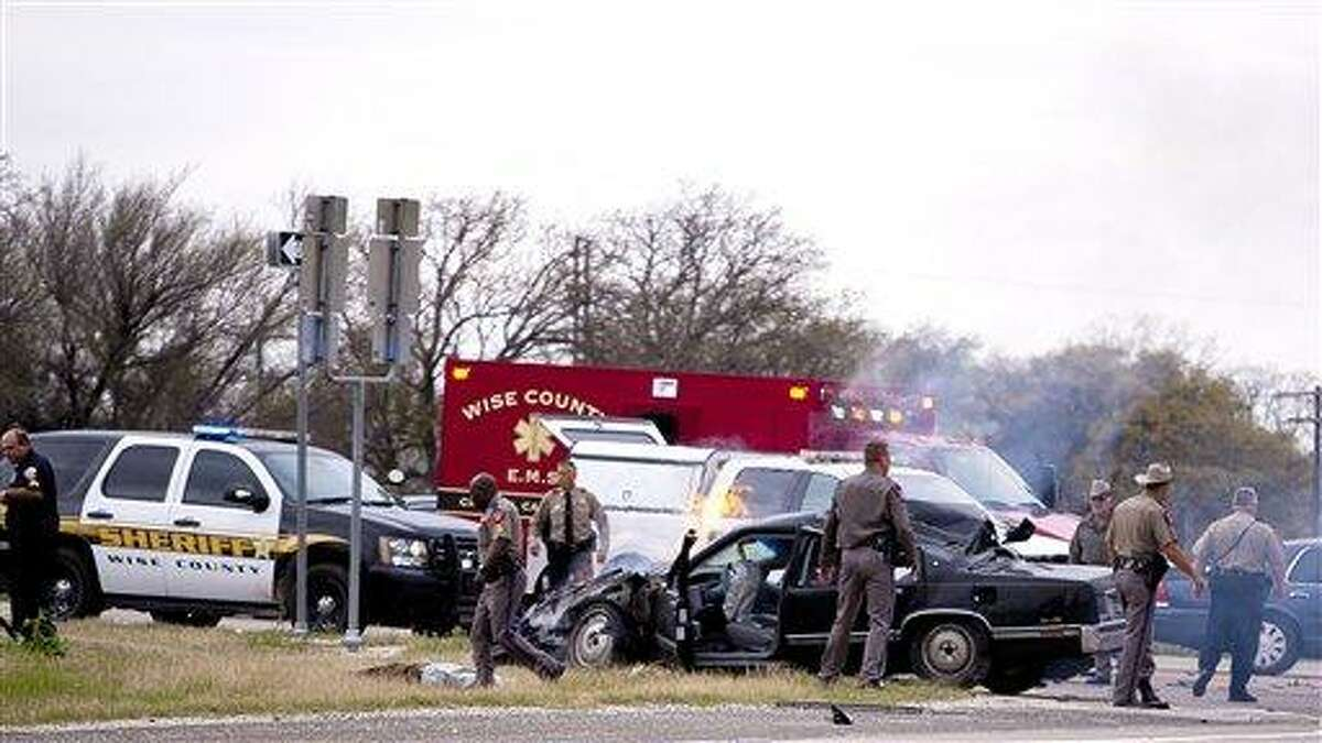 Emergency personnel are on the scene of a crash and shootout with police involving the driver of a black Cadillac with Colorado plates in Decatur, Texas, Thursday, March 21, 2013. The driver led police on a gunfire-filled chase through rural Montague County, crashed his car into a truck in Decatur, opened fire on authorities and was shot, officials said. Texas authorities are checking whether the Cadillac is the same car spotted near the home of Colorado prisons chief Tom Clements, who was shot and killed when he answered the door Tuesday night. (AP Photo/Wise County Messenger, Jimmy Alford, Mags Out)