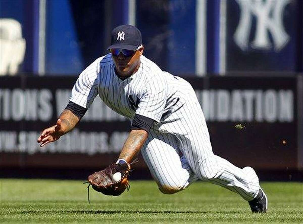 New York Yankees' Andruw Jones dives and catches a ball hit by Toronto Blue Jays' Adam Lind during the sixth inning in a baseball game, Wednesday, Aug. 29, 2012, at Yankee Stadium in New York. The umpires ruled that he dropped the ball as his body hit the ground and was ruled a single. (AP Photo/Rich Schultz)