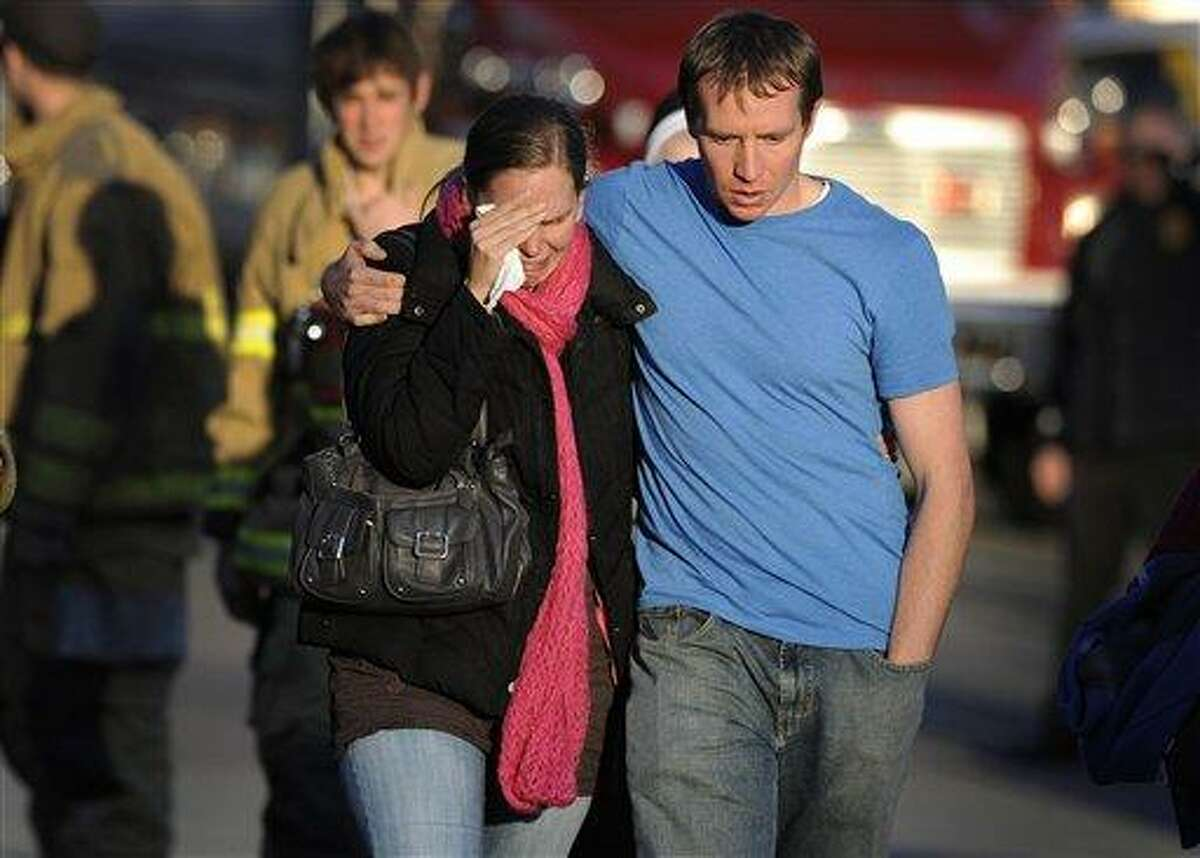 FILE - In this Dec. 14, 2012 file photo, Alissa Parker, left, and her husband, Robbie Parker, leave the firehouse staging after receiving word that their six-year-old daughter Emilie was one of the 20 children killed in the Sandy Hook School shooting in Newtown, Conn. Alissa Parker told