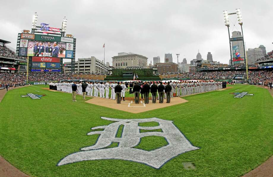 Umpires line up, keeping open a spot to honor umpire Wally Bell, who died Monday of a heart attack, during the national anthem before Game 3 of the American League championship series between the Tigers and the Boston Red Sox on Tuesday in Detroit. Photo: Matt Slocum — The Associated Press  / AP