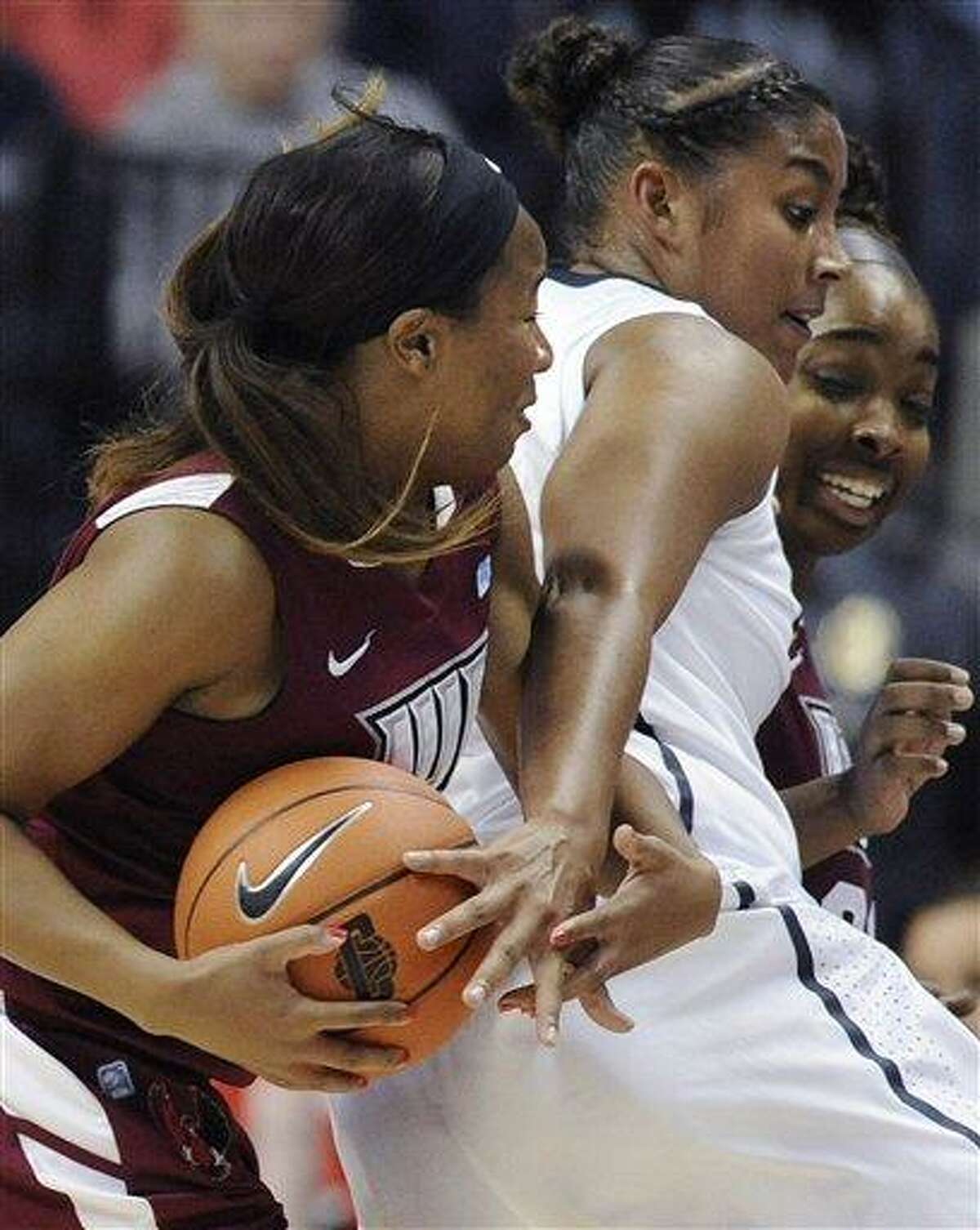 Connecticut's Kaleena Mosqueda-Lewis, center, reaches for the ball between Indiana of Pennsylvania's Talen Watson, left, and Lisa Burton, right, during the first half of a college exhibition basketball game in Storrs, Conn., Friday, Nov. 2, 2012. (AP Photo/Jessica Hill)
