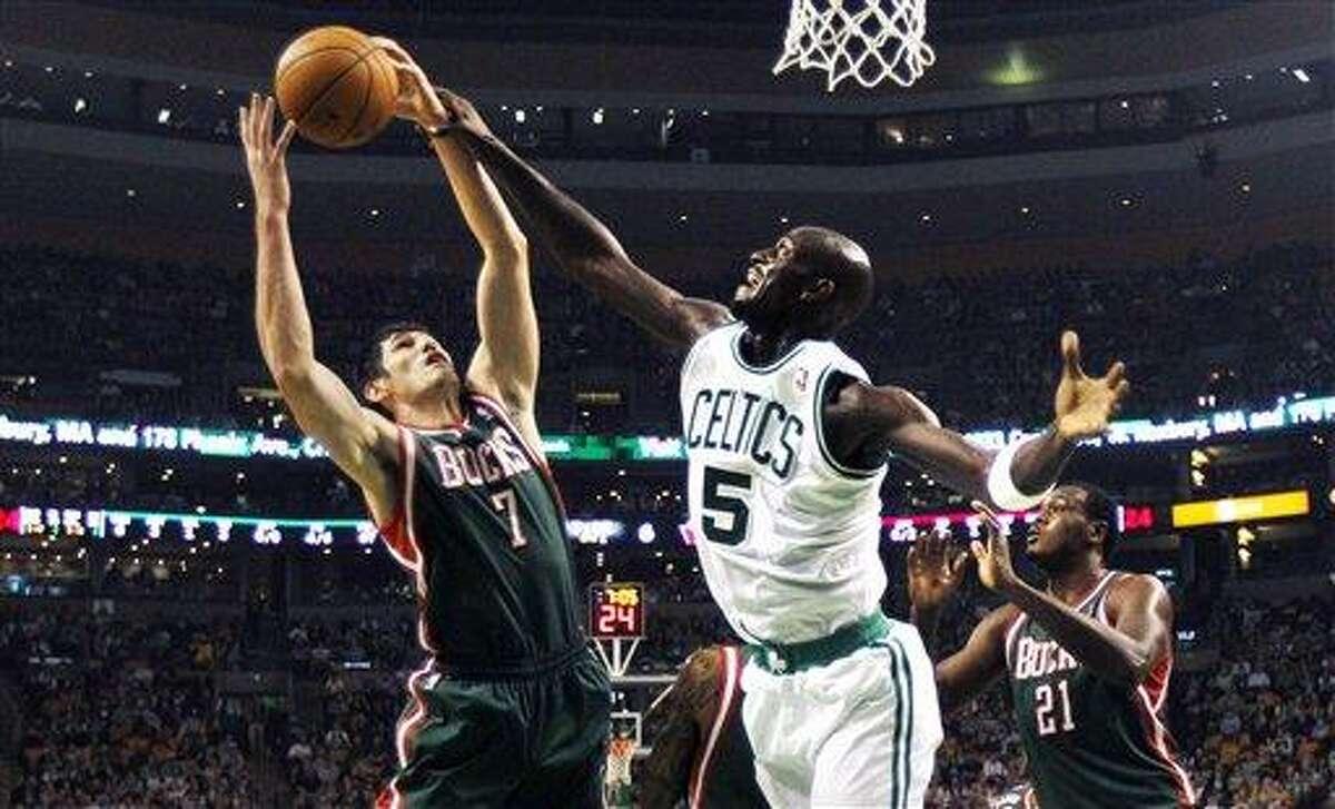 Boston Celtics forward Kevin Garnett, right, battles for a rebound against Milwaukee Bucks forward Ersan Ilyasova, of Turkey, in the first quarter of an NBA basketball game in Boston, Friday, Nov. 2, 2012. (AP Photo/Charles Krupa)