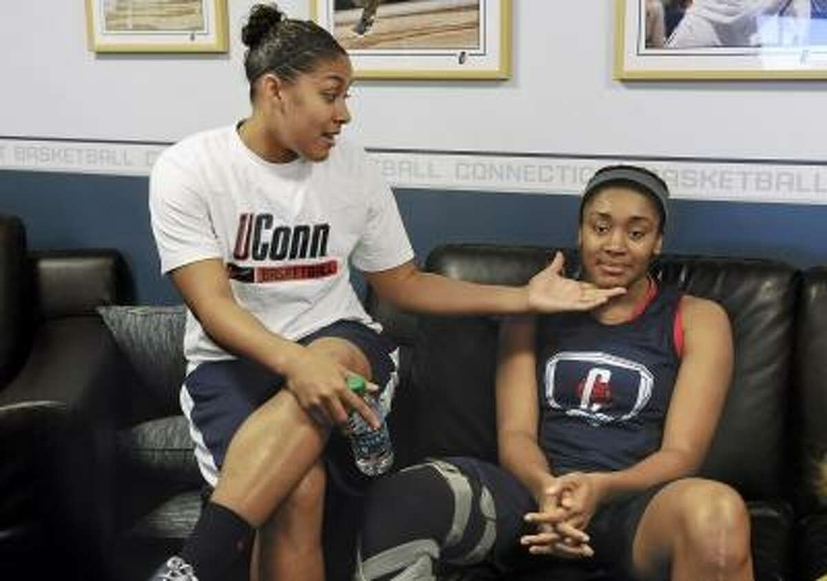 Connecticut's Kaleena Mosqueda-Lewis, left, and Morgan Tuck share a playful moment in their locker room before practice for a first-round game. Photo by Jessica Hill/Associated Press