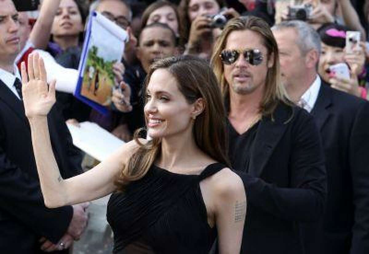 """U.S. actress Angelina Jolie arrives with her partner U.S. actor Brad Pitt (R) for the world premiere of his film """"World War Z"""" in London June 2, 2013."""