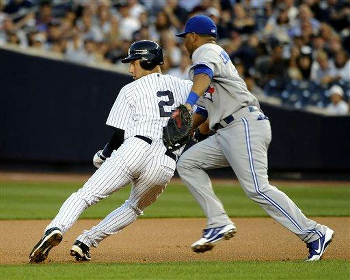 New York Yankees' Derek Jeter (2) is tagged out by Toronto Blue Jays first baseman Edwin Encarnacion in the first inning of a baseball game on Tuesday, Aug., 28, 2012, in New York. (AP Photo/Kathy Kmonicek)