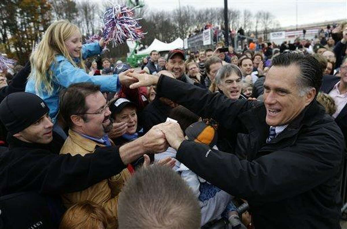 Republican presidential candidate and former Massachusetts Gov. Mitt Romney greets supporters as he campaigns at Portsmouth International Airport, in Newington, N.H. Saturday. AP Photo/Charles Dharapak