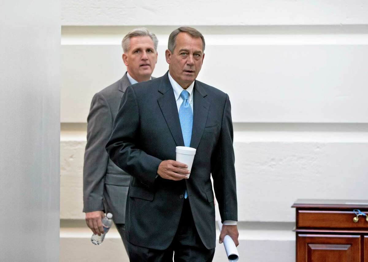 Speaker of the House John Boehner, R-Ohio, with House Majority Whip Kevin McCarthy, R-Calif., left, walks to a meeting of House Republicans at the Capitol in Washington, Tuesday, Oct. 15, 2013, as a partial government shutdown enters its third week. It is not yet clear how Boehner and tea party members in the House majority will respond to the Senate's Democratic and Republican leaders closing in on a deal to avoid an economy-menacing Treasury default and end the partial government shutdown. (AP Photo/J. Scott Applewhite)