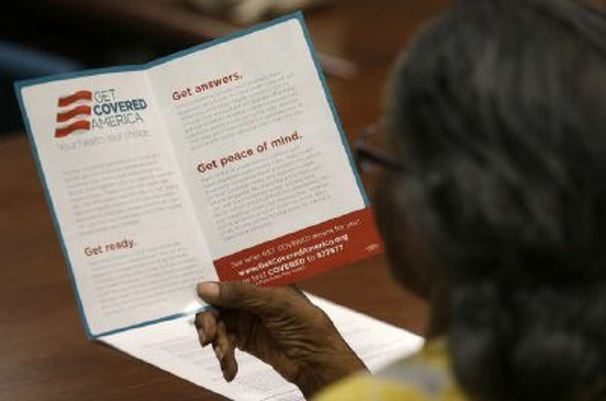 Eufaula Frazier, a volunteer with Enroll America in Miami, a private, non-profit organization running a grassroots campaign to encourage people to sign up for health care offered by the Affordable Care Act, reads over a pamphlet before making calls to inform people of their health care options in Miami.