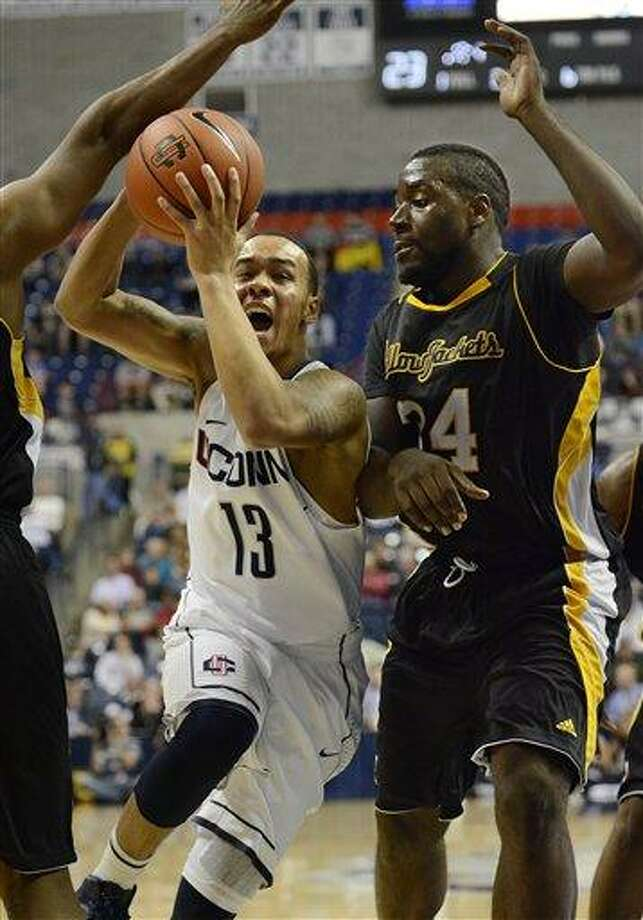 Connecticut Shabazz Napier (13) drives to the basket while guarded by American International College's David Campbell (34) during the first half of a men's NCAA basketball game in Storrs, Conn., Thursday, Nov. 1, 2012. (AP Photo/Jessica Hill) Photo: AP / FR125654 AP