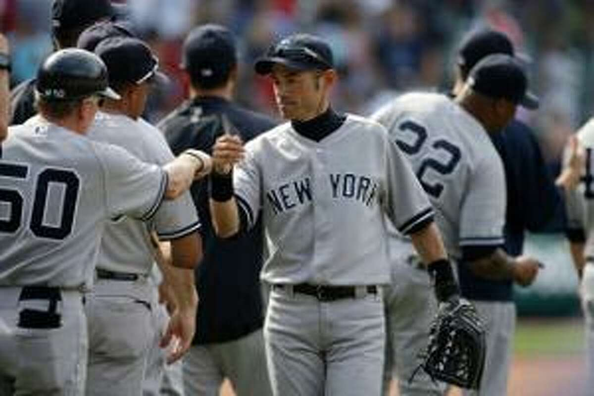 ASSOCIATED PRESS New York Yankees right fielder Ichiro Suzuki celebrates with first base coach Mick Kelleher (50) after a 4-2 win over the Cleveland Indians on Sunday in Cleveland.