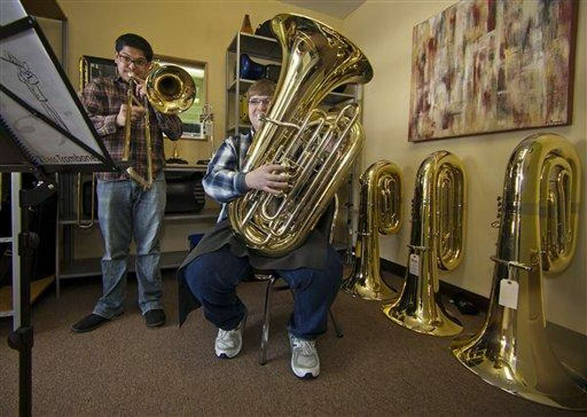 In this recent photo, University of Redlands students -- trombonist Ben Solis 28, left, and master tuba player Victor Mortson, 23 -- play their instruments at The Horn Guys store in La Crescenta, Calif. Someone who is breaking into high schools from the East Side of Los Angeles to the shores of Manhattan Beach and stealing expensive tubas to supply a fast-growing banda black market. Associated Press