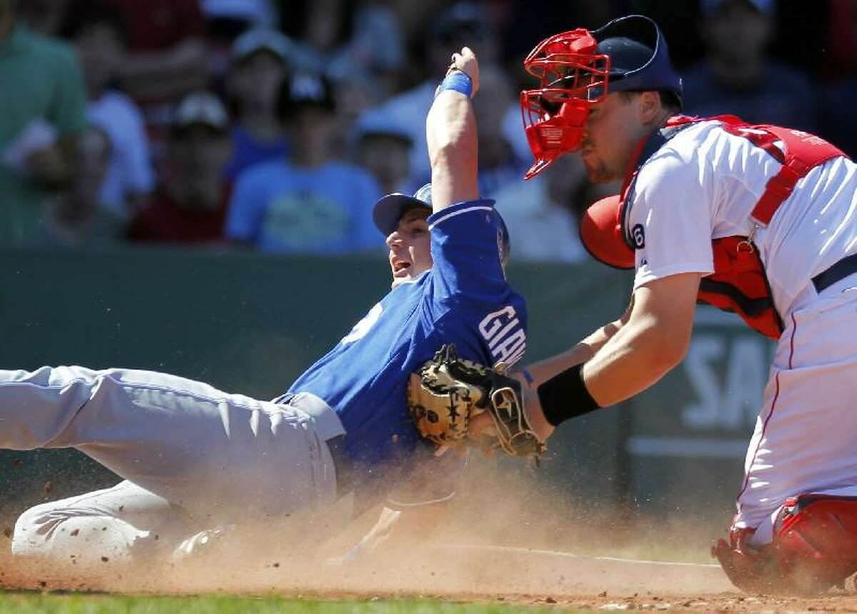ASSOCIATED PRESS Kansas City Royals' Johnny Giavotella, left, scores on an RBI single by Tony Abreu as Boston catcher Ryan Lavarnway, right, tries to make the play in the fourth inning of Sunday's game at Fenway Park in Boston. The Red Sox won 8-6.
