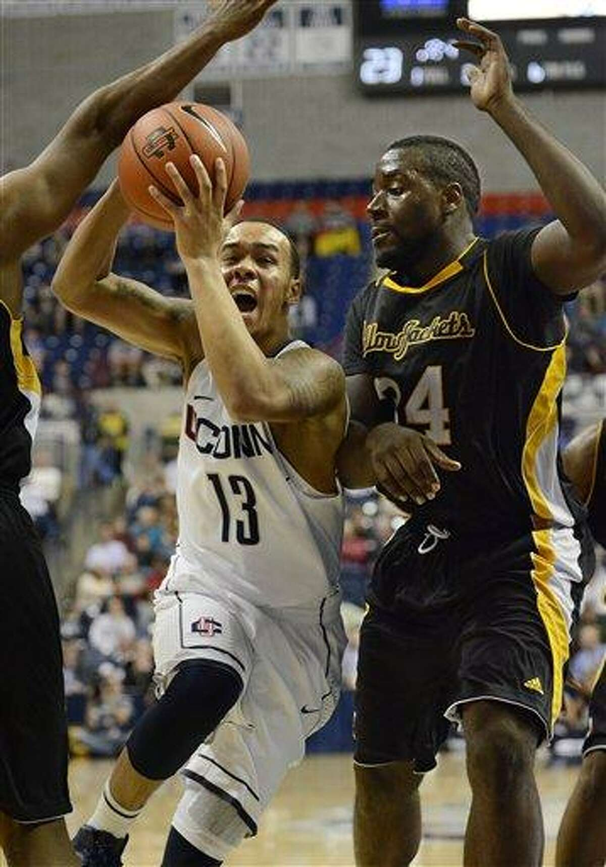 Connecticut Shabazz Napier (13) drives to the basket while guarded by American International College's David Campbell (34) during the first half of a men's NCAA basketball game in Storrs, Conn., Thursday, Nov. 1, 2012. (AP Photo/Jessica Hill)