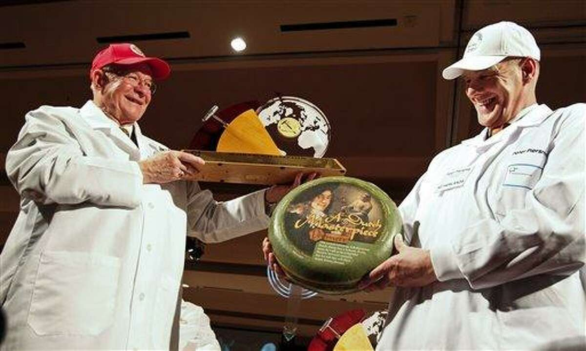 Bill Schlingsog, left, of Middleton, Wis., passes off the championship trophy to Peter Piersma, a judge and representing the Netherlands, at the 2012 World Champion Cheese Contest Wednesday in Madison, Wis. The top winning gouda was made by Freisland Campina company in Wolvega, Netherlands. Associated Press