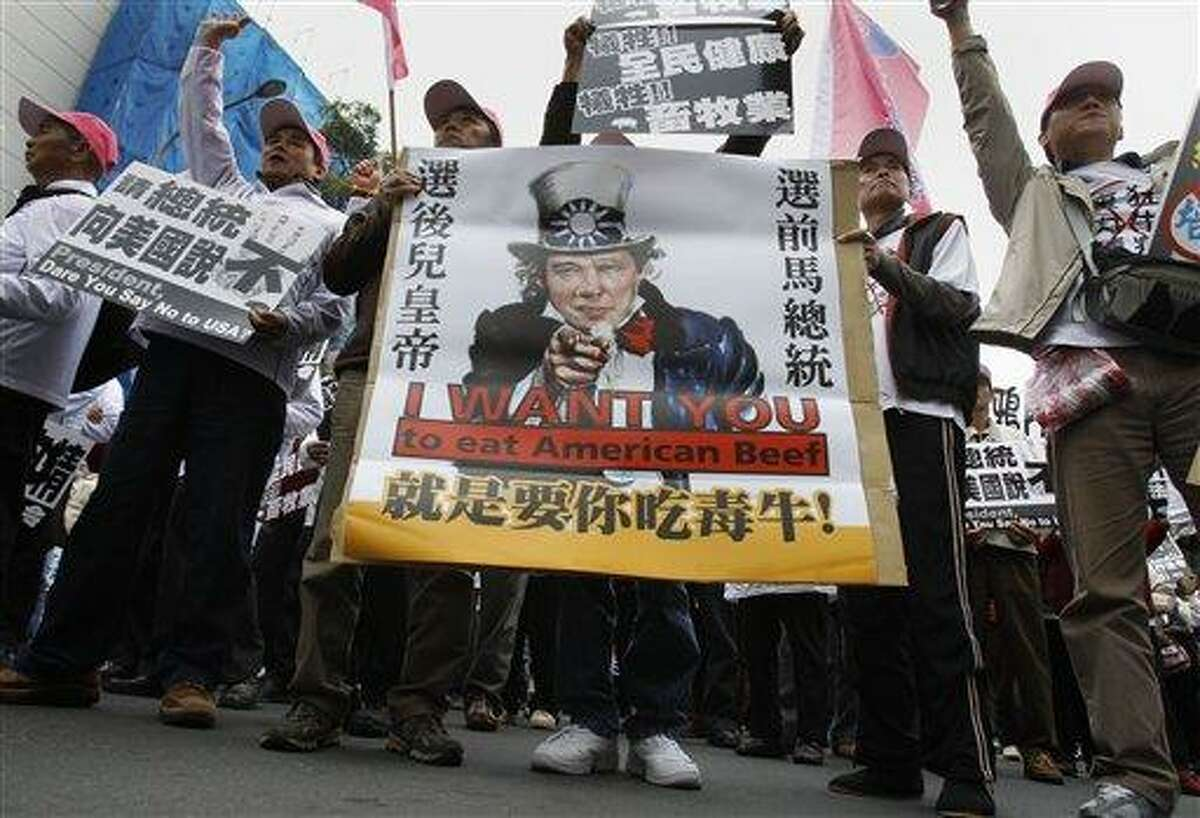 """Using an image of American icon """"Uncle Sam"""" with Taiwanese President Ma Ying-jeou's face imposed, thousands of Taiwanese stage a protest in front of the Legislature against the government's plan to import U.S. beef containing the growth additive ractopamine. Associated Press"""