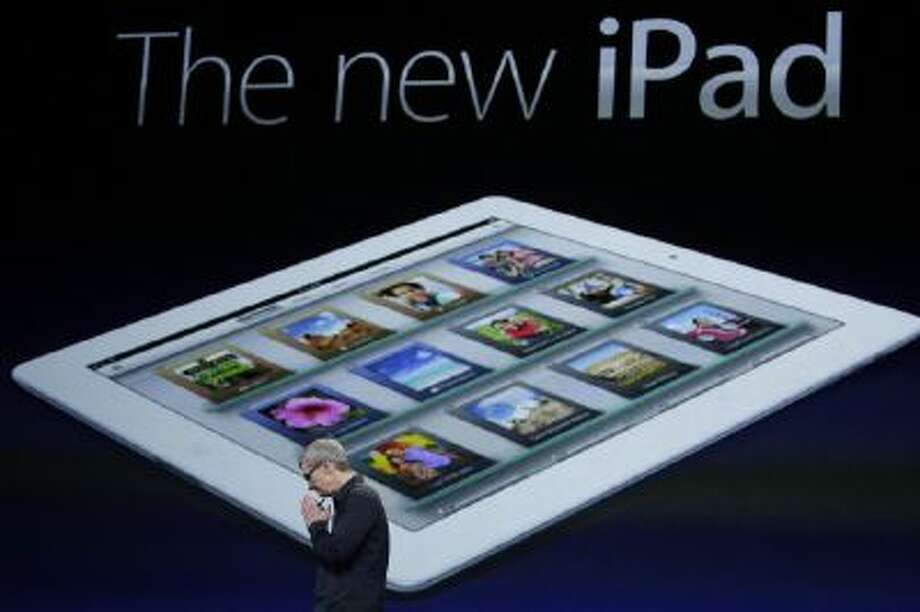 Apple CEO Tim Cook clasp his hands during an iPad event in 2012.