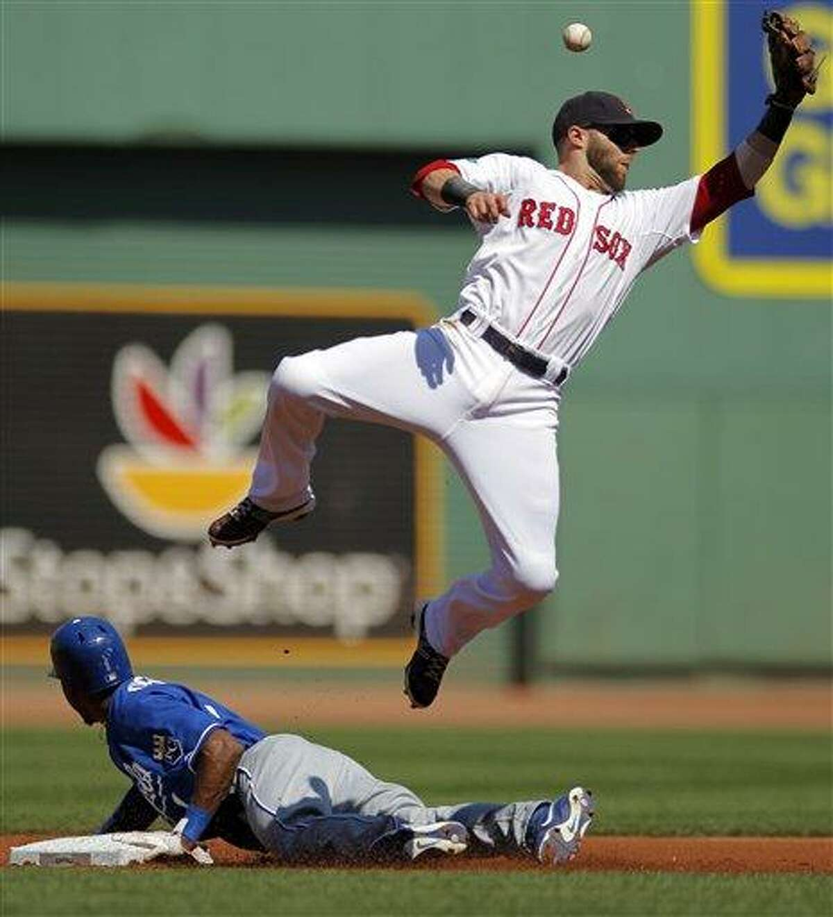 Kansas City Royals' Jarrod Dyson, bottom, steals second base as Boston Red Sox's Dustin Pedroia tries to get his glove on the ball in the first inning of a baseball game at Fenway Park, Monday, Aug. 27, 2012. (AP Photo/Steven Senne)