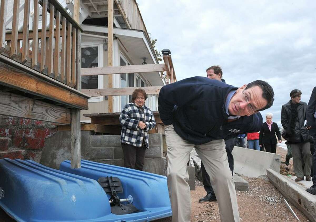New Haven-- Governor Dannel Malloy looks under a deck at damage in Morris Cove from Hurricane Sandy. Malloy and other government officials visited the area Friday afternoon. Photo--Peter Casolino/New Haven Register. 11/02/12