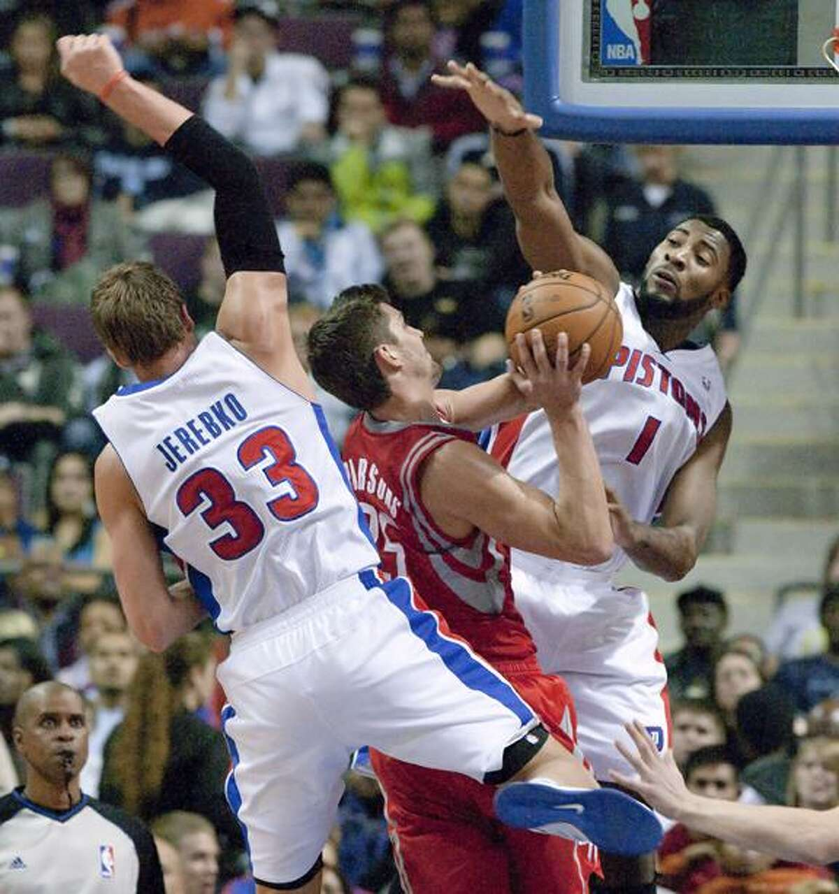 Detroit Pistons forwards Jonas Jerebko (33) and Andre Drummond (1) put pressure on Houston Rockets forward Chandler Parsons as he goes to the basket in the fourth quarter of an NBA basketball game Wednesday, Oct. 31, 2012, in Detroit. The Rockets defeated the Pistons 105-96. (AP Photo/Duane Burleson