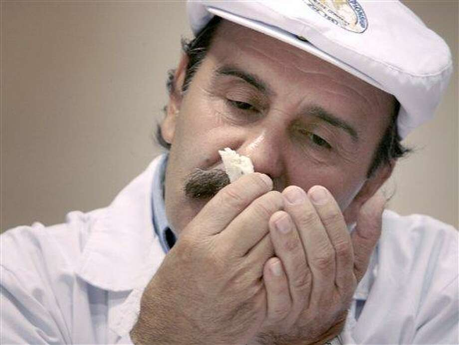 Judge Roberto Castenega of Argentina, samples the aroma of one of the entries in the Semi-soft Goat's Milk Cheese category during the opening day of the World Championship Cheese Contest at the Monona Terrace Convention Center in Madison, Wis. on Monday, March 5, 2012.  More than 2,500 entries will be judged throughout the three day gathering, sponsored every two years by the Wisconsin Cheese Makers Association.   (AP Photo/Wisconsin State Journal, John Hart ) Photo: AP / Wisconsin State Journal