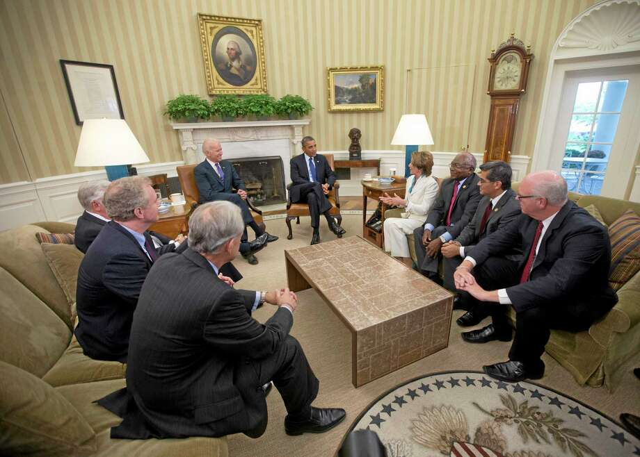 President Barack Obama, center, and Vice President Joe Biden, center left,  meet with Democratic Leadership in the Oval Office of the White House, Tuesday, Oct. 15, 2013, in Washington. Sitting with them clockwise from the bottom left, Rep. Steve Israel, D-N.Y., Rep. Chris Van Hollen, D-Md., Rep. Steny Hoyer, Md., House Minority Leader Nancy Pelosi of Calif., Rep. James Clyburn, D-S.C., Rep. Xavier Becerra, D-Calif., Rep. Joseph Crowley, D-N.Y. The partial government shutdown is in its third week and less than two days before the Treasury Department says it will be unable to borrow and will rely on a cash cushion to pay the country's bills. (AP Photo/Pablo Martinez Monsivais) Photo: AP / AP