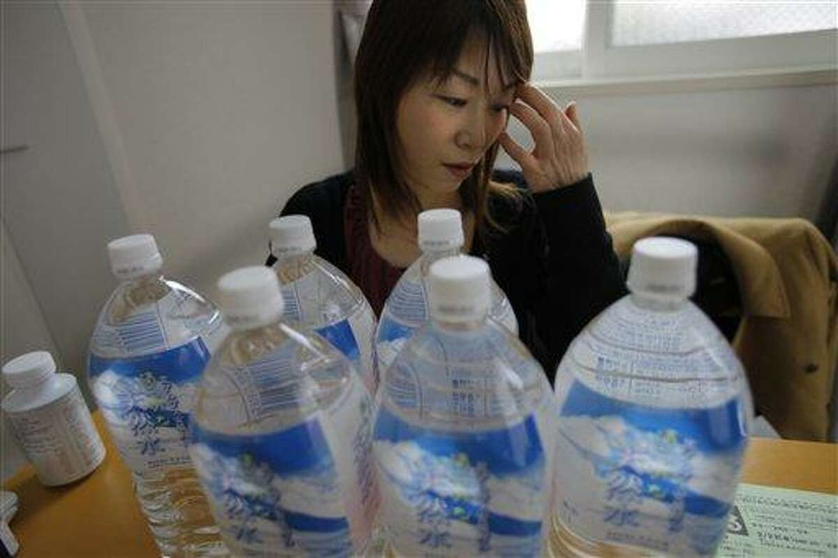 In this February photo, Yoshiko Ota displays the bottled water she bought at a local shop for daily use at her house in Fukushima, Japan. Ota keeps her windows shut. She never hangs her laundry outdoors. Fearful of birth defects, she warns her daughters: Never have children. This is life with radiation, nearly one year after a tsunami-hit nuclear power plant began spewing it into Ota's neighborhood, 40 miles (60 kilometers) away. Associated Press