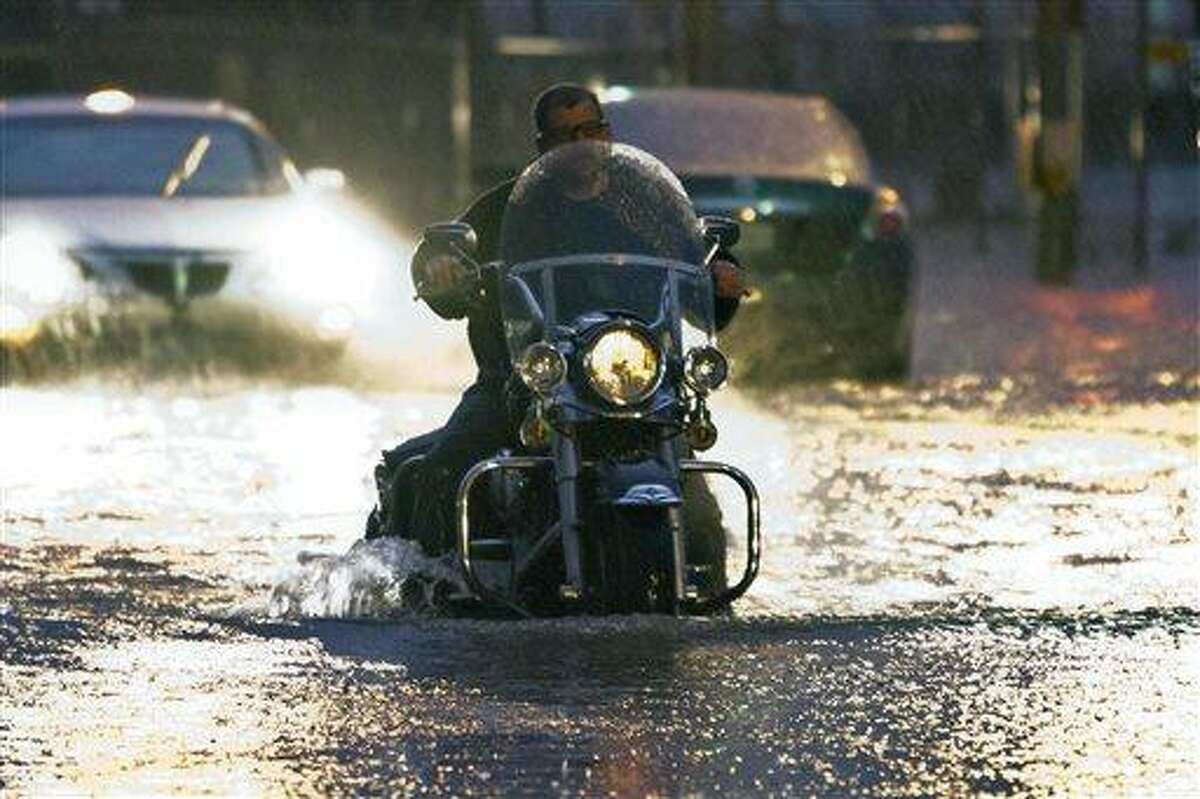 A man on a motorcycle drives through flood water on Western Ave. at NW 5th Street in Oklahoma City on Friday, May 31, 2013. (AP Photo/Alonzo Adams)