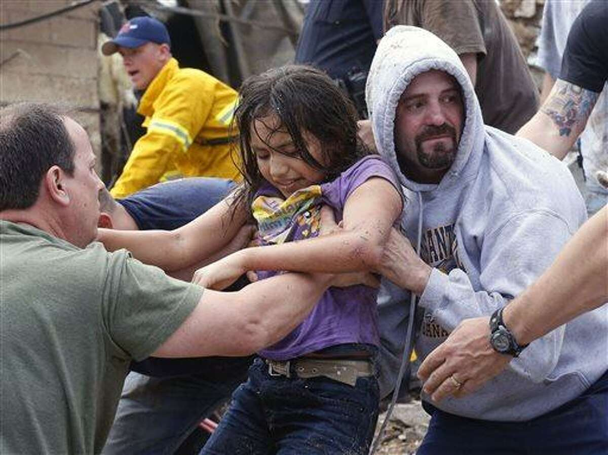 A child is passed along a human chain of people after being pulled from the rubble of the Plaza Towers Elementary School in Moore, Okla., and passed along a human chain of rescuers Monday, May 20, 2013. A tornado as much as half a mile (.8 kilometers) wide with winds up to 200 mph (320 kph) roared through the Oklahoma City suburbs Monday, flattening entire neighborhoods, setting buildings on fire and landing a direct blow on an elementary school. (AP Photo Sue Ogrocki)