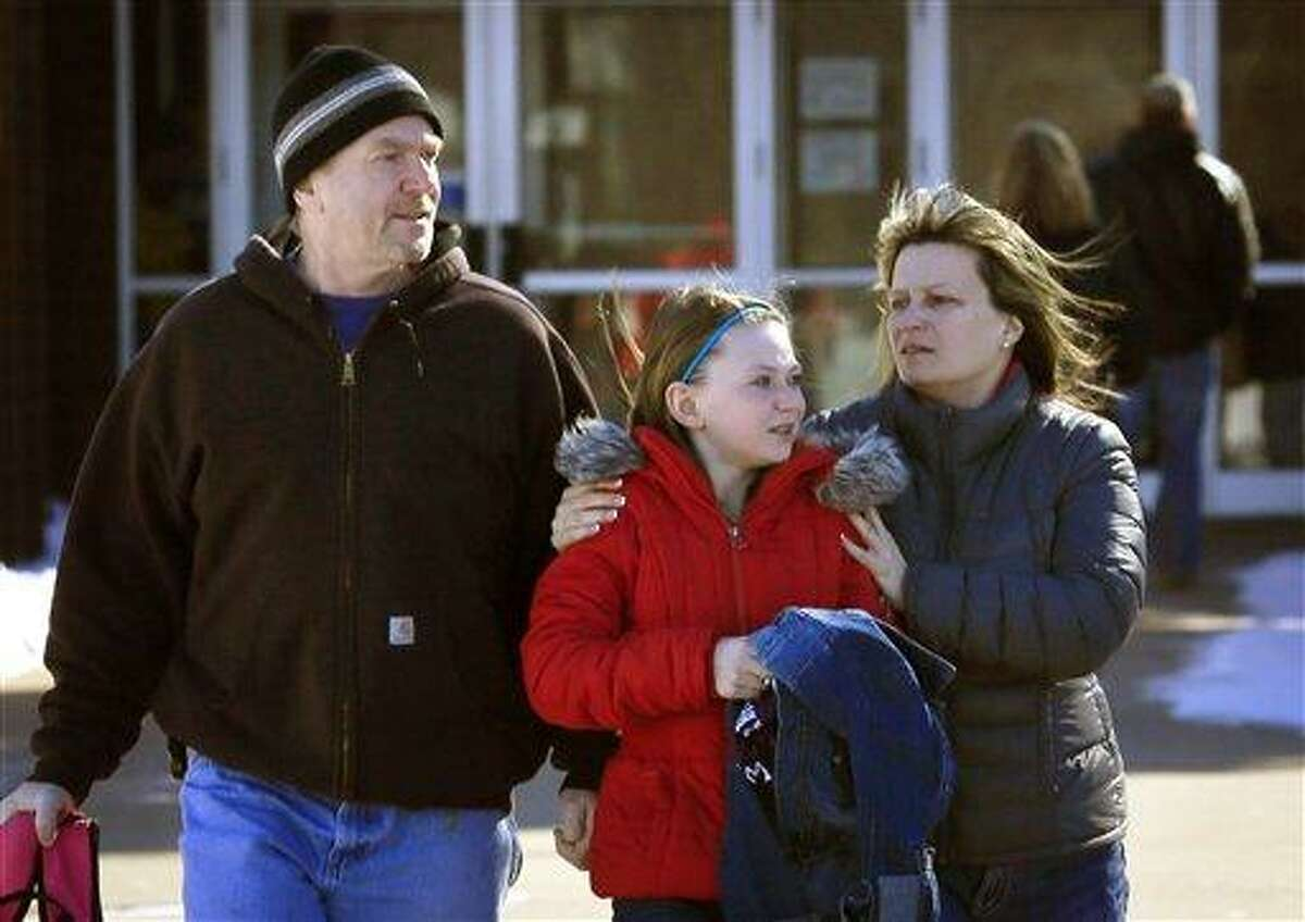 """Parents pick up their child at New Prague Middle School in New Prague, Minn., Wednesday, March 20, 2013, after authorities responded to a 911 call concerning an """"active shooter"""" at the middle school, but a staff member later said everyone is safe and there is no danger inside the building. The 911 call in which a caller claimed several people had been gunned down at the school was likely a hoax, Scott County Sheriff Kevin Studnicka said said Wednesday. (AP Photo/The Star Tribune, Brian Peterson)"""