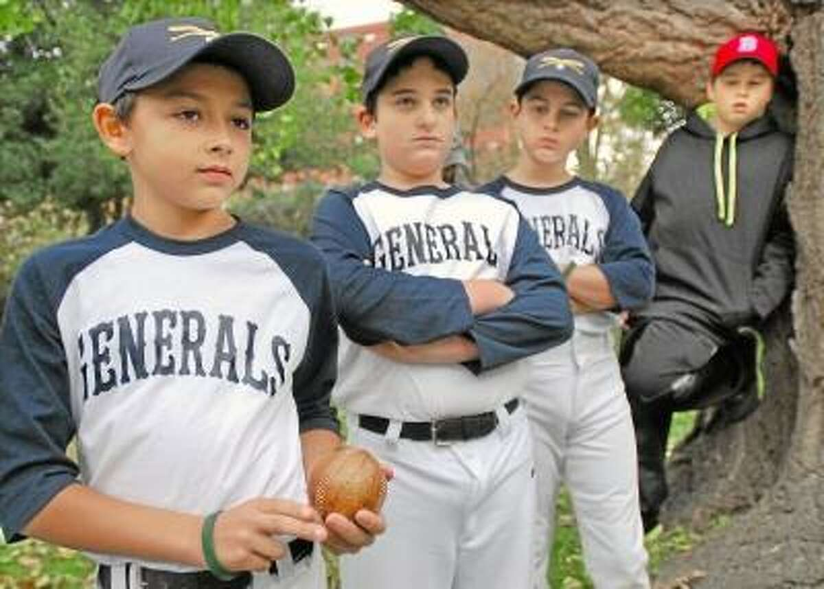 Catherine Avalone/The Middletown Press Members of the the Middletown Generals (left to right) Jacob Texidor, 11, Antonio Milardo, 11, and Logan Wenzel, 10, pass a vintage baseball around while listening to local baseball historian and author Bill Ryczek tell the history of the Middletown Mansfields in the garden at the Middlesex Historical Society Thursday afternoon. Milardo, a first baseman, wrote a school paper on the Mansfields, Middletown's professional baseball team in the late 19th century. He suggested the city's Little League All-Star team name itself after the Mansfields' namesake: General Joseph Mansfield.