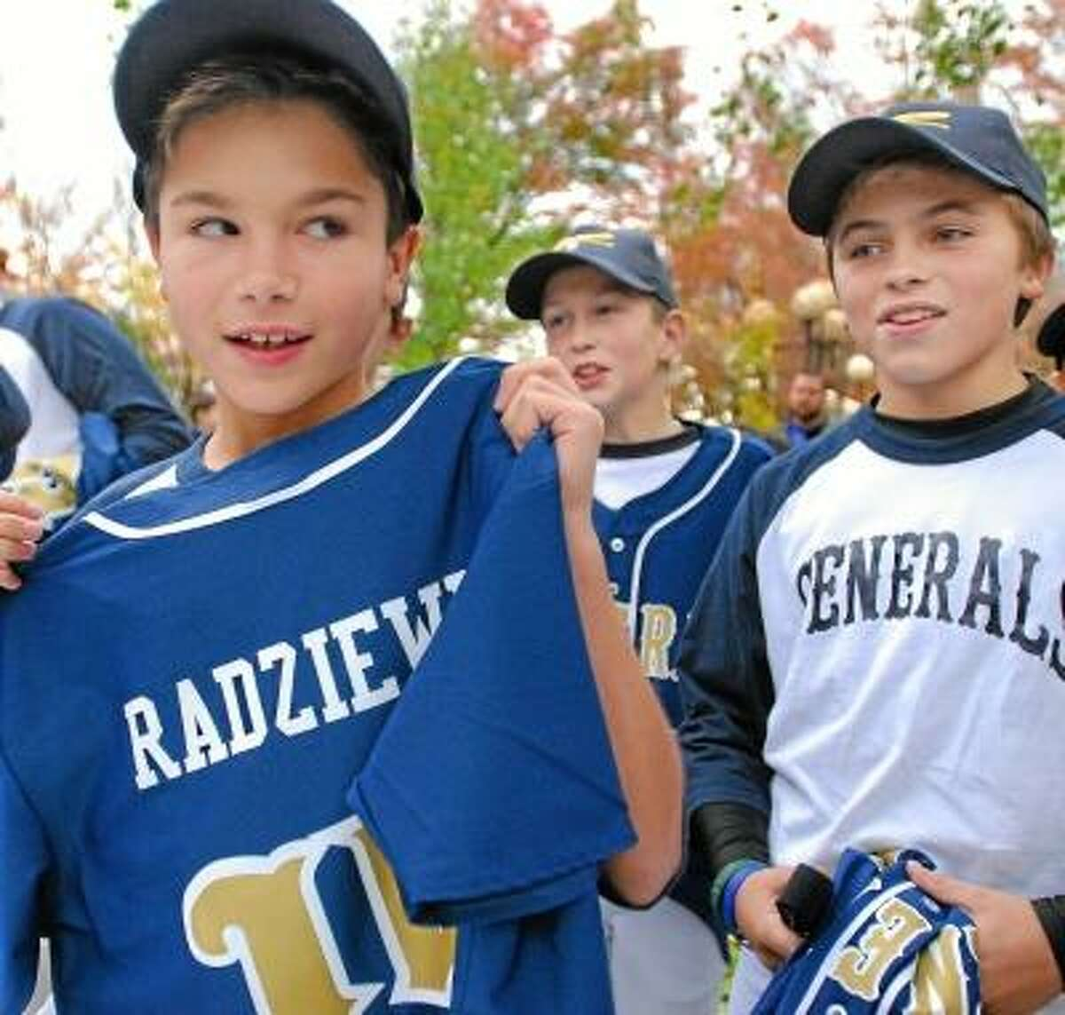 Catherine Avalone/The Middletown Press Shortstop for the Middletown Generals, Lucas Radziewicz, 10, holds up his new team jersey in the garden at the Middlesex Historical Society Thursday afternoon. At right is Greyson Pizzonia. The team is named after General Joseph Mansfield.