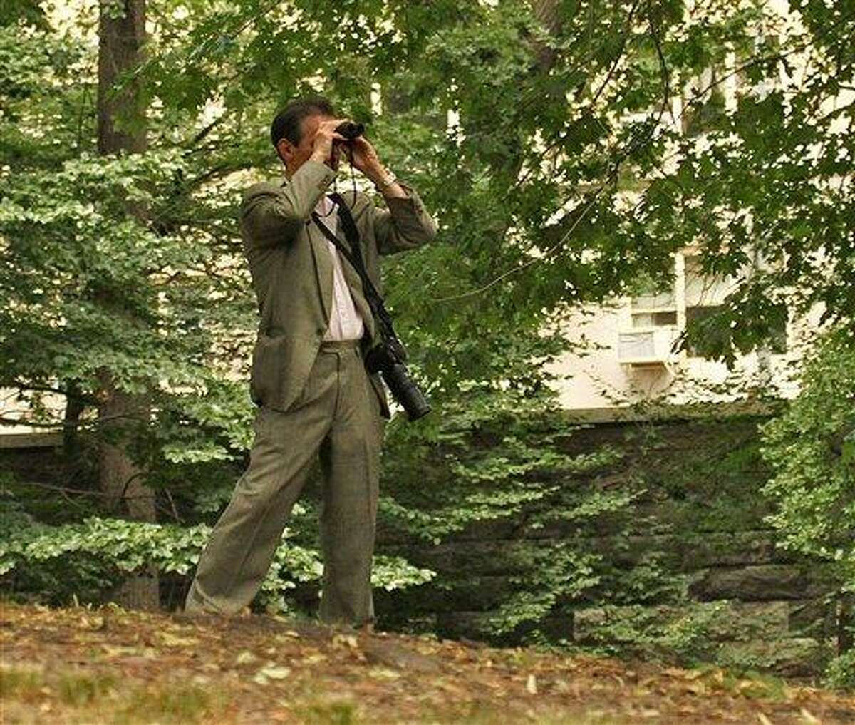 In this June 30, 2012 photo provided by Jean Shum, Jeffrey Johnson uses binoculars to search New York's Central Park for the young offspring of a popular red-tailed Hawk that local birdwatchers know as Pale Male. On Friday, Aug. 24, 2012, Johnson killed a former employer outside the Empire State Building in New York and was himself killed shortly afterwards by police. Nine bystanders were wounded in that chaotic confrontation. (AP Photo/Jean M. Shum) MANDATORY CREDIT