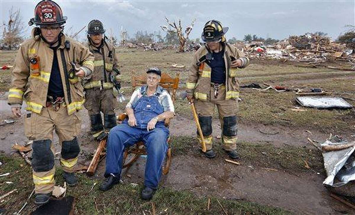 Oklahoma City fire fighters check on the status of Gene Tripp as he sits in his rocking chair where his home once stood after being destroyed by a tornado hit the area near 149th and Drexel on Monday, May 20, 2013 in Oklahoma City, Okla. (AP Photo/The Oklahoman, Chris Landsberger)