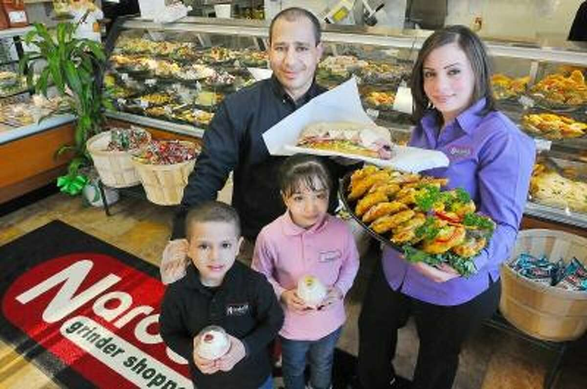 Catherine Avalone/The Middletown Press Cromwell resident Hani Shehata and his wife, Suzan, pictured with their two children, Emily 7, and Jacob, 5 display a few of Nardelli favorites, the Italian Combo grinder, a platter of Prosciutto Hot Pepper Chicken, Cheesecake and Yogurt parfaits. The Shehata's opened Nardelli's Grinder Shoppe in Cromwell Commons at 136 Berlin Road on Route 372 in Cromwell a week ago today. Hours are Monday through Saturday from 9 a.m. to 9 p.m. The Cromwell store is the eighth Nardelli's location in Connecticut.