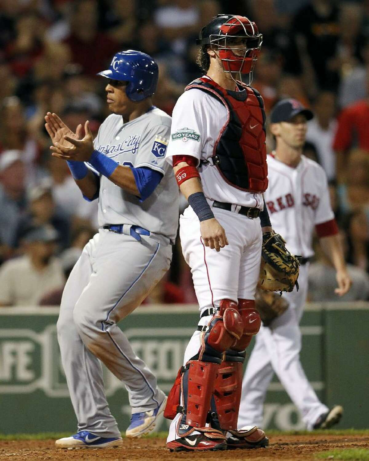 ASSOCIATED PRESS Kansas City Royals' Salvador Perez, left, scores the tying run behind Boston Red Sox's Jarrod Saltalamacchia on a two-run triple by Royals' Mike Moustakas in the seventh inning of Saturday night's game at Fenway Park in Boston. The Red Sox lost 10-9.