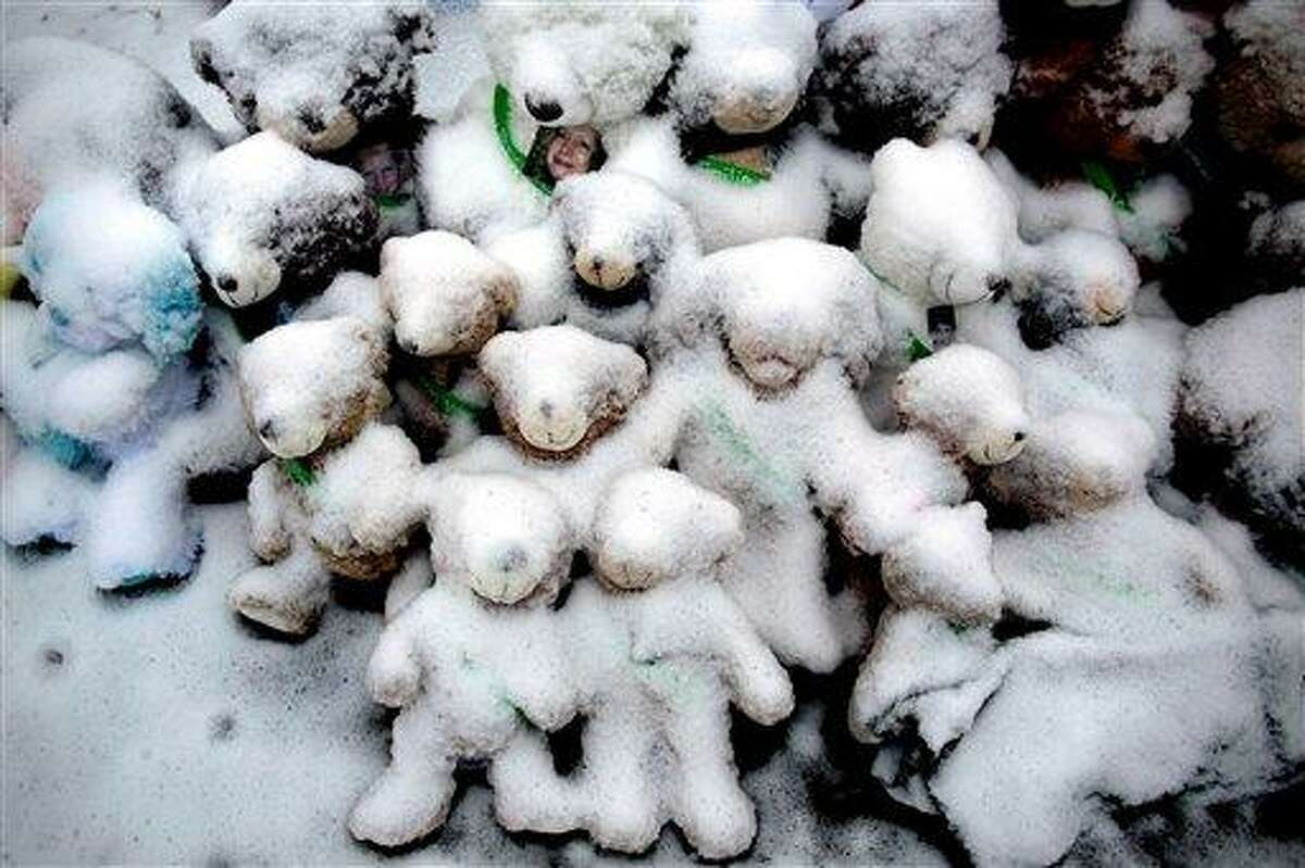 Snow-covered stuffed animals with photos attached sit at a memorial Dec. 25 in Newtown. Associated Press file photo