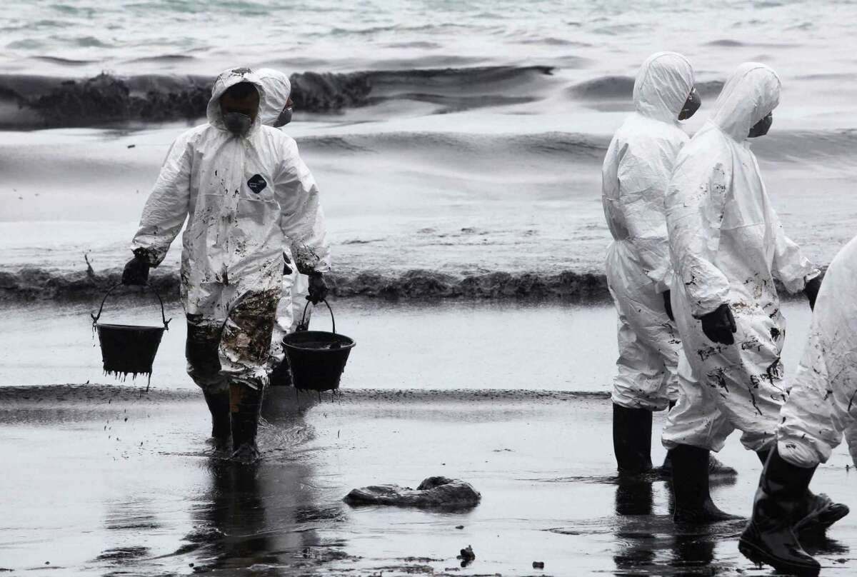 Workers use buckets to remove crude oil during a clean up operation on the beach of Prao Bay on Samet Island in Rayong province eastern Thailand Tuesday, July 30, 2013. About 50,000 liters (13,200 gallons) of crude oil that leaked from a pipeline operated by PTT Global Chemical Plc, has reached the popular tourist island in Thailand's eastern sea despite continuous attempts to clean it up. (AP Photo)