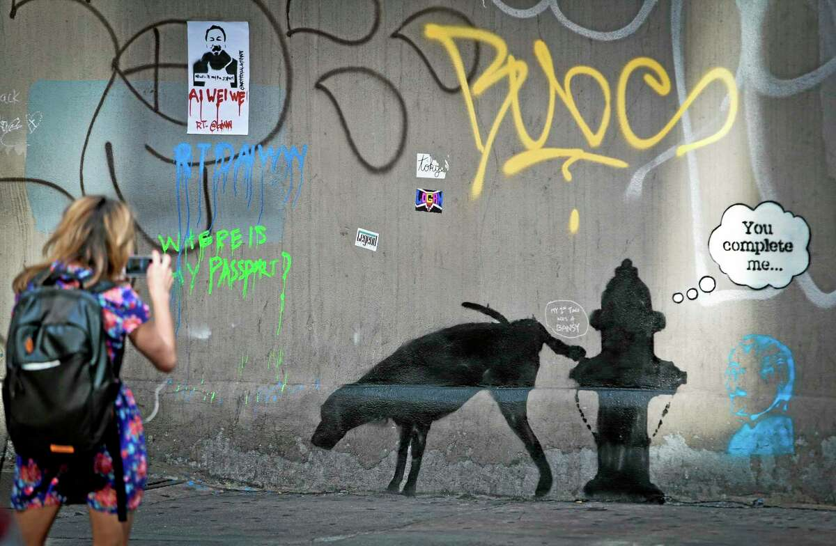 FILE - In this Friday, Oct. 4, 2013, file photo, graffiti by the secretive British artist Banksy, featuring a dog and a fire hydrant, draws attention on 24th Street, near Sixth Avenue in New York. Banksy wrote on his website that he had set up a stall in New York's Central Park on Saturday, Oct. 12, 2013, with original signed works, selling for only $60 apiece. His works typically sell for thousands of dollars. (AP Photo/Bebeto Matthews, File)