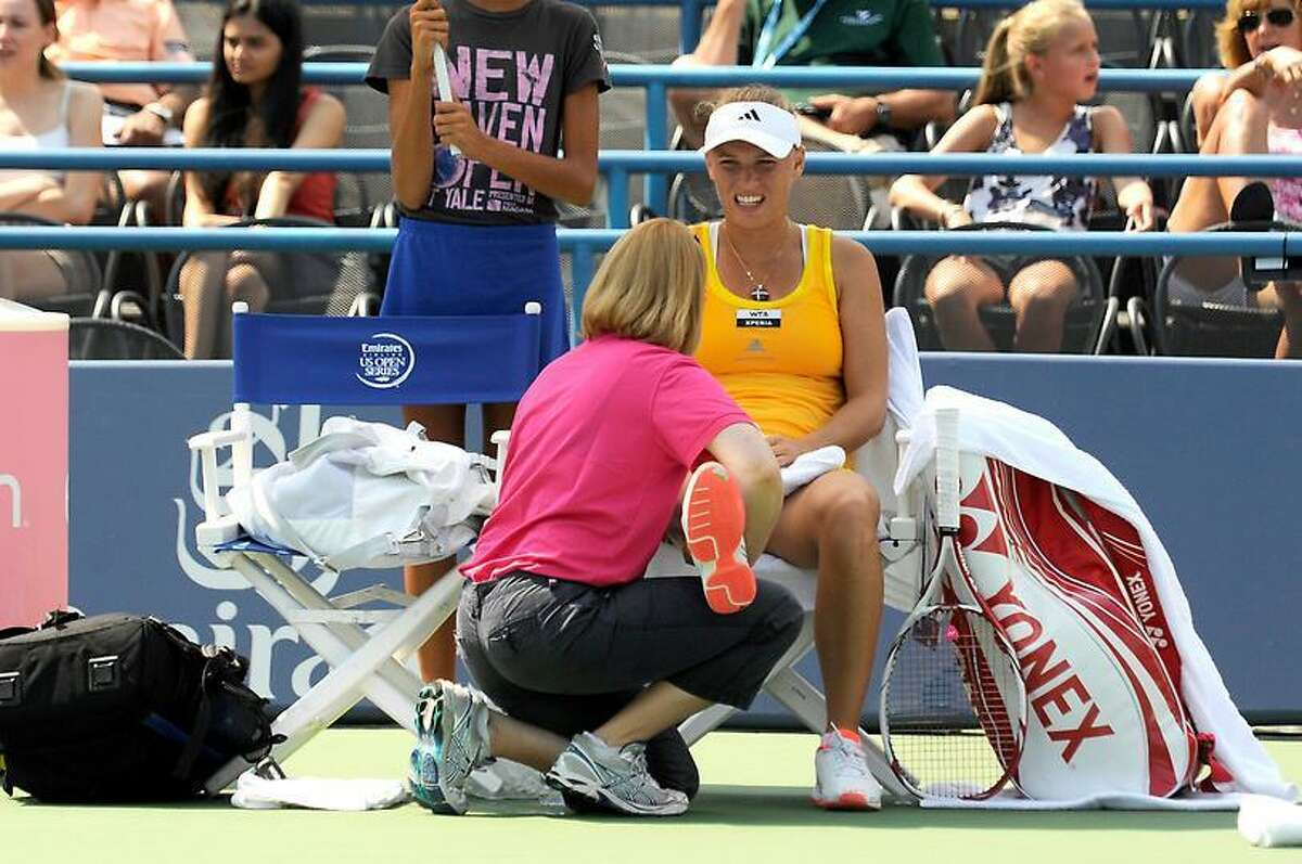 Caroline Wozniacki receives treatment for her knee during her quarterfinal singles match at the New Haven Open Thursday, Aug. 23, 2012. (Bob Child/Special to the Register)