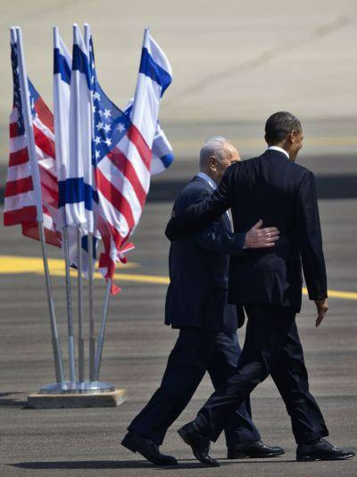 US President Barack Obama, right, and Israel's President Shimon Peres walk together at the end of welcoming ceremony upon Obama's arrival at Ben Gurion airport near Tel Aviv, Israel, Wednesday, March 20, 2013. President Barack Obama is declaring common cause with Israel, highlighting the bonds between the United States and its Mideast ally. He says he has made Israel the first stop of the first trip of his second term to restate his commitment to Israel's security. (AP Photo/Ariel Schalit)