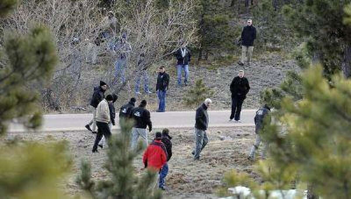 Investigators search the wooded area surrounding the home of Tom Clements, executive director of the Colorado Dept. of Corrections, on Colonial Park Drive east of Monument Wednesday morning.