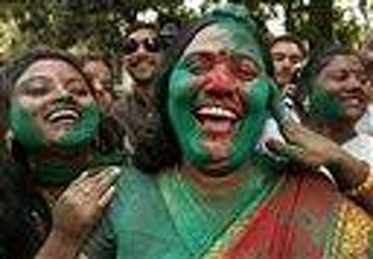 Samajwadi Party supporters smear each others' faces with colored powder as they celebrate an early lead of the party leader Mulayam Singh Yadav in Uttar Pradesh state election in Lucknow, India. Election officials across five Indian states Tuesday began counting votes in crucial provincial elections that are being seen as a test of strength for the country's ruling Congress party. Associated Press