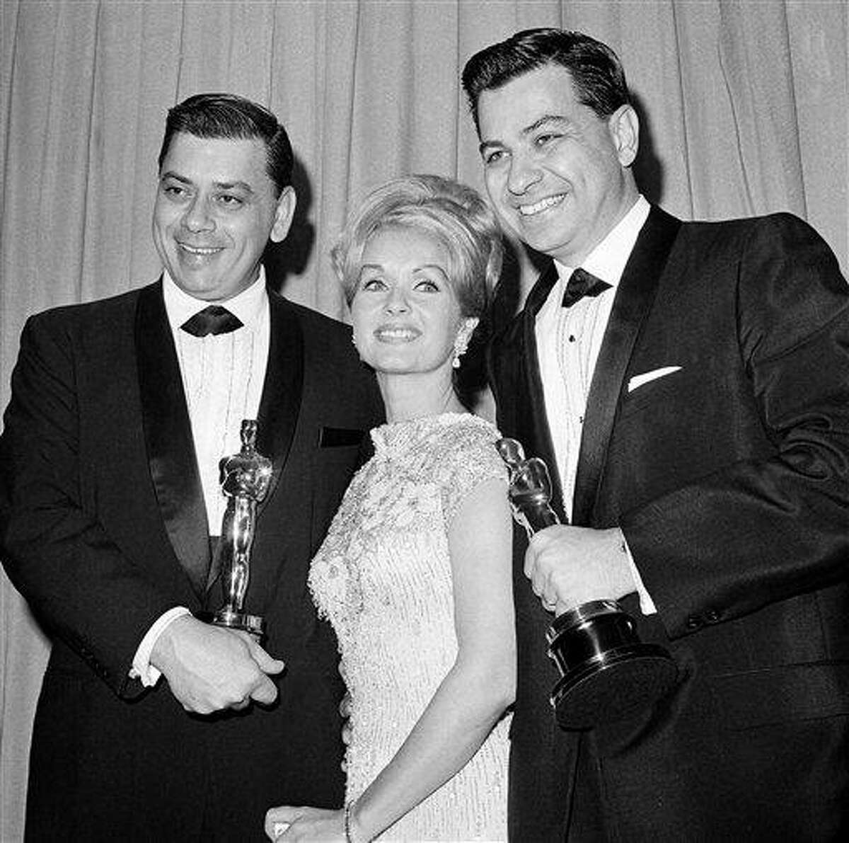 """In this 1965 file photo, actress Debbie Reynolds poses with Academy Awards winners for best music Richard M. Sherman, right, and Robert Sherman, left, who received the award for """"Mary Poppins"""" in Santa Monica Calif. Songwriter Sherman, who wrote the tongue-twisting """"Supercalifragilisticexpialidocious"""" and other enduring songs for Disney classics, has died. He was 86. Associated Press"""