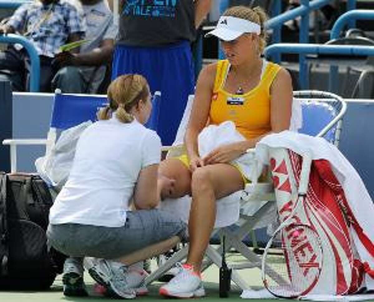 ASSOCIATED PRESS Caroline Wozniacki, of Denmark, speaks with trainer Kerri Whitehead before retiring from her semifinal match after losing the first set 7-5 against Maria Kirilenko, of Russia, at the New Haven Open tennis tournament in New Haven on Friday. A right knee injury suffered in the quarterfinals forced the retirement.