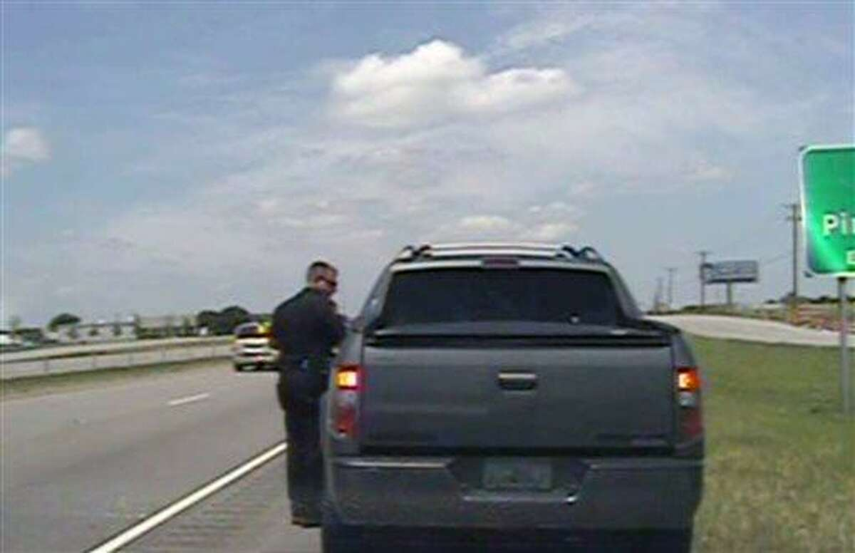 In this image taken from dashcam video provided by the City of Forney Police Department, a police officer speaks with George Zimmerman, the neighborhood watch volunteer acquitted by a Florida jury of charges in the fatal shooting of a black teenager, after he was pulled over for speeding along U.S. 80, about 20 miles east of Dallas on Sunday, July 28, 2013. Zimmerman was released with a warning. (AP Photo/City of Forney Police Department)